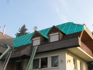 Tetőfelújítás egy II. kerületi családi házon. Pala borítás eltávolítása, légáteresztő fólia rögzítése, rejtett ereszcsatorna elbontásának elkezdése.